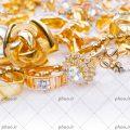 عکس با کیفیت انگشتر های طلایی داخل گردنبند مروارید به رنگ طلایی از نمای نزدیک