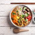 عکس با کیفیت چوب مخصوص نودل در کنار ظرف نودل با سبزیجات و دو ظرف سس مخصوص نودل