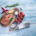 عکس با کیفیت تکه ای از ماهی خام بر روی تخته گوشت و سبزیجات در اطراف