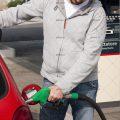 عکس با کیفیت مرد ایستاده در کنار ماشین قرمز و در حال بنزین زدن با نازل
