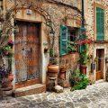 عکس با کیفیت کوچه با خانه های قدیمی و کوچه پر شده از گلدان های زیبا و پنجره های فیروزه ای