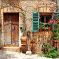 عکس با کیفیت خانه با در چوبی قدیمی و دیوار خانه تزئین شده با گلدان های زیبا و پنجره فیروزه ای