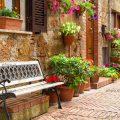 عکس با کیفیت نیمکت در کنار دیوار خانه پر از گلدان های زیبا و پنجره چوبی