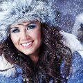 عکس با کیفیت زن در روز برفی با کلاه و کاپشن خز دار آبی