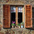 عکس با کیفیت خانه با دیوار سنگی با پنجره چوبی باز و گلدان های زیبا در کنار پنجره و دیده شدن پرده ی